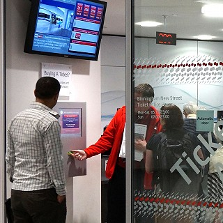 A Virgin Trains employee shows a customer how to use the new ticket machine