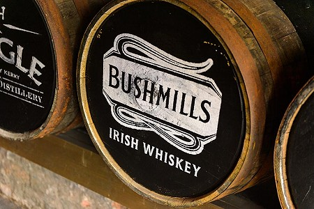 Wooden whiskey barrels containing irish whiskey by Bushmills distillery