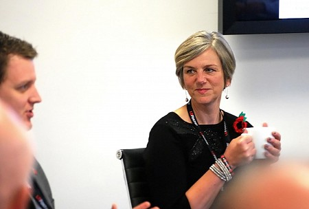 A blonde haired woman in a white meeting room holds a mug while engaging in conversation