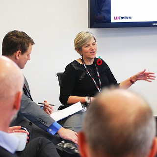 A blonde haired woman in a white meeting room speaking to a group of people