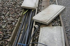 Cabling running alongside rail tracks, damaged and removed.