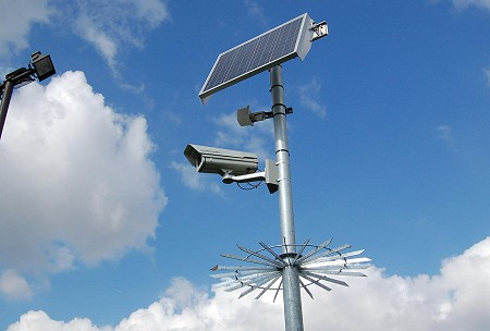 A solar powered mounted security camera against a blue sky