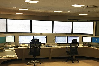 Five large screens mounted above six smaller screens on a work station. There are two chairs at the station