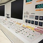 A power station control room with many buttons and switches and dials