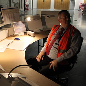 A man in a red tie, wearing a high visibility jacket sits at a desk lit by a small lamp