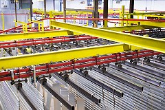 A top down view of a yellow and red overhead conveyor carrying metal slats