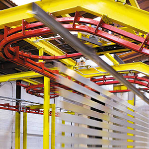 A yellow and red overhead conveyor carrying metal slats