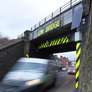 A bridge with a white van driving under it