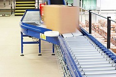 A large cardboard box travelling quickly along a blue roller conveyor