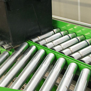 A green roller conveyor carries a black plastic crate along