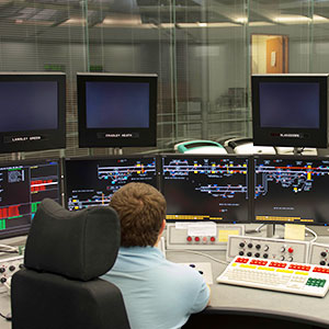 Man sitting at a signalling desk with multiple monitors, switches and dials