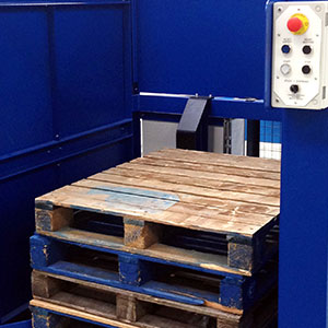 A blue Staktec machine with wooden pallets placed inside