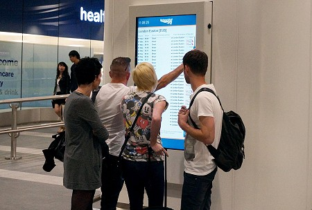Two women and two men stand around a large touchscreen in a train station